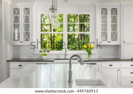 Kitchen interior detail in new home with island, two sinks, window view of vibrant green trees, pendant lights, and cabinetry with lights off
