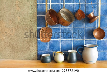 Kitchen interior. Hanging retro design copper kitchenware set. Pots, stewpots, coffee maker, spoon, skimmer. Different sizes, colors pitchers on the wooden table. Blue tiles and aged wall background. - stock photo
