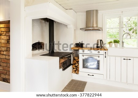 kitchen interior in a country house with brick wall and antique wood stove - stock photo