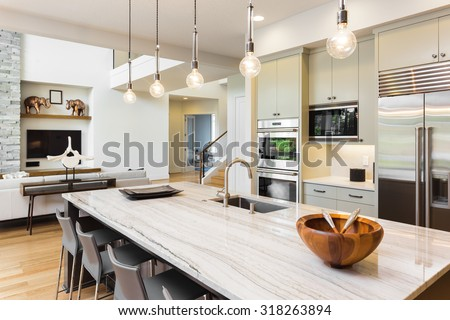 Kitchen Interior in New Luxury Home with Island, Sink, Cabinets, and Hardwood Floors and View of Living Room - stock photo