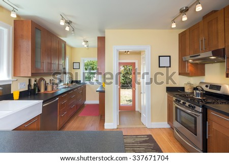 Kitchen interior in wood with counter top and island. Bright walls, granite counter tops and stainless steel appliances.  - stock photo