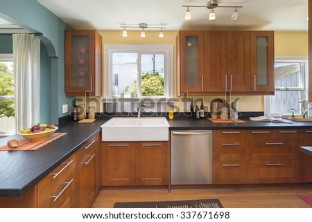 Kitchen interior in wood with dark granite marble black counter tops and stainless steel appliances.  - stock photo