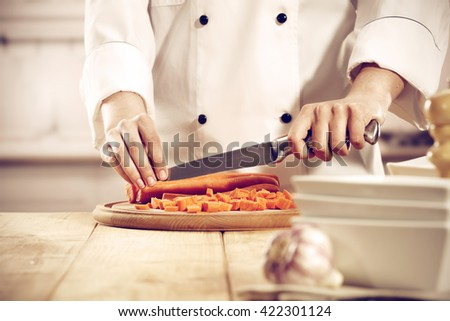 kitchen interior with big yellow wooden table place and cook hands and knife  - stock photo