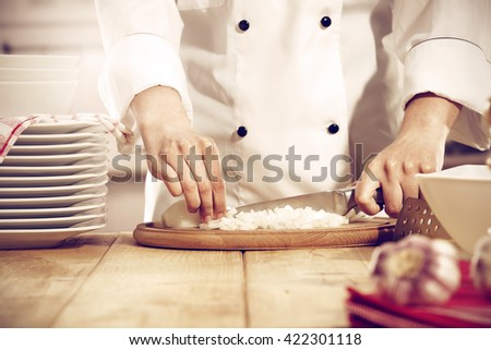 kitchen interior with big yellow wooden table place and onion and hands  - stock photo