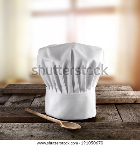 kitchen interior with cook hat and single wooden spoon  - stock photo
