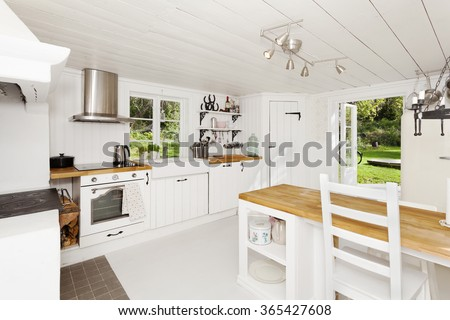kitchen interior with open door out to the garden - stock photo