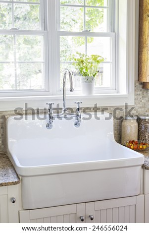 Kitchen interior with rustic white porcelain sink and granite stone countertop under large sunny window - stock photo