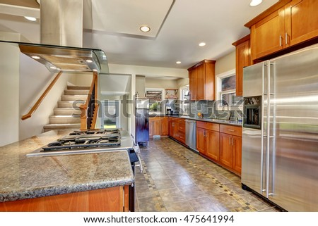 Kitchen interior with tile flooring and modern brown cabinets, mosaic green backsplash and stainless steel appliances. Northwest, USA