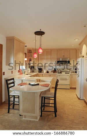 Kitchen interior with updated maple wood cabinetry cork floors and quartz countertops under pendant lights - stock photo