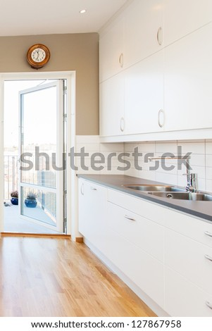 kitchen interior with white cupboards and a open door out to the balcony - stock photo