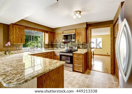 Kitchen interior with wooden cabinets, tile floor and granite counter top - stock photo