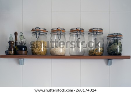 kitchen jars on a shelf on a wall of white tiles - stock photo