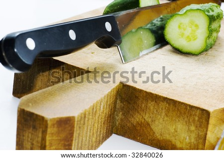 kitchen knife and cucumber on wood table - stock photo