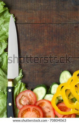 Kitchen knife and sliced vegetables lying on wooden surface with copy space - stock photo