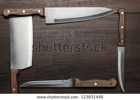 kitchen knifes on the brown wooden table - stock photo