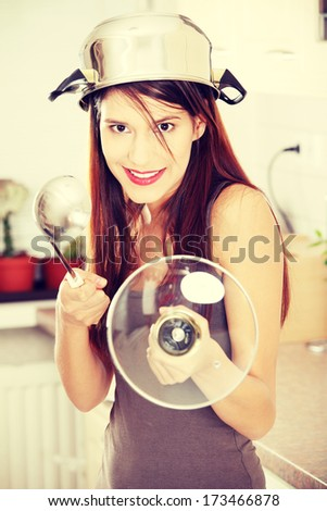 Kitchen Knight - young beautiful caucasian woman in kitchen with pot on her head (as helmet) and hohl (as sword) - stock photo