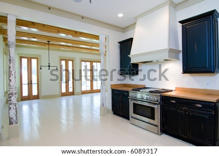 kitchen remodel in rustic motif with reclaimed pillars, looking into living area - stock photo