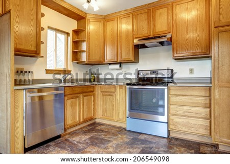 Kitchen room interior with brown tile floor, honey tone storage combination with steel appliances - stock photo