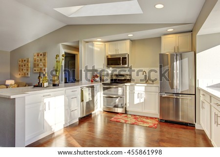 Kitchen room interior with white cabinets, hardwood floor and rug