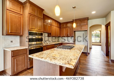 Kitchen room interior with wooden cabinets with granite counter top and island. Northwest, USA