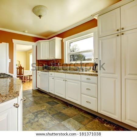 Kitchen room with concrete floor, orange walls and white storage combination. - stock photo