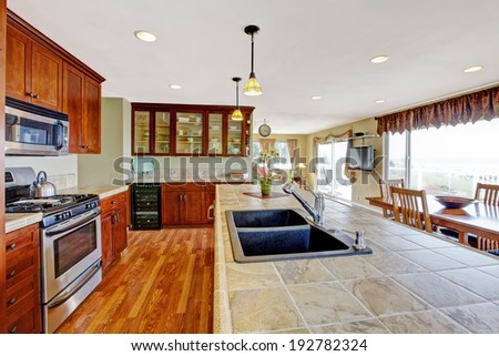 Kitchen room with dining area. View of kitchen island with built-in sink. - stock photo