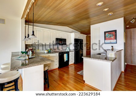 Kitchen room with paneled ceiling, white cabinets with black appliances. Granite counter top with bar stools - stock photo