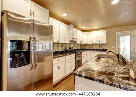 Kitchen room with white appliances, granite counter top, kitchen island and hardwood floor