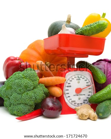 kitchen scale and vegetables on a white background close-up. vertical photo. - stock photo