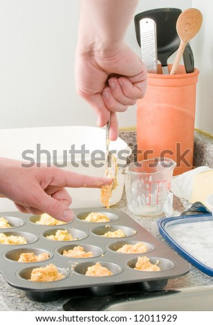 Kitchen scene of a  person making muffins