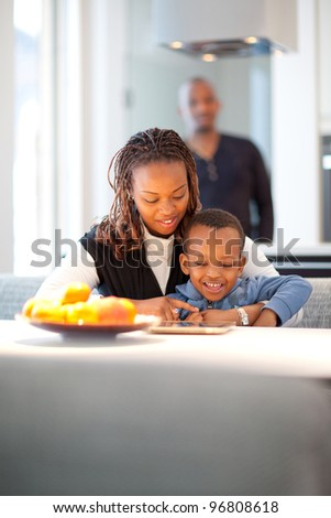 Kitchen setting with young black family playing with a tablet pc. - stock photo