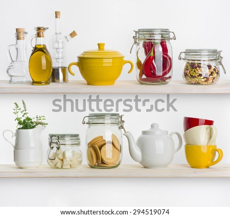 Kitchen shelves with various food ingredients and utensils on white - stock photo