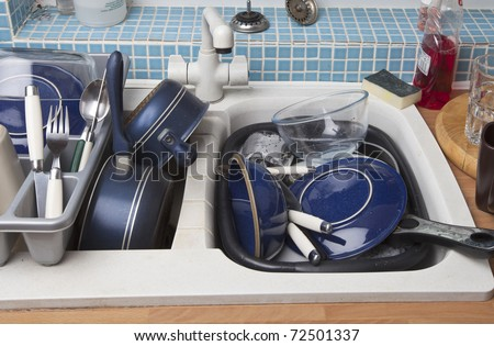 kitchen sink full of dirty dishes for washing up