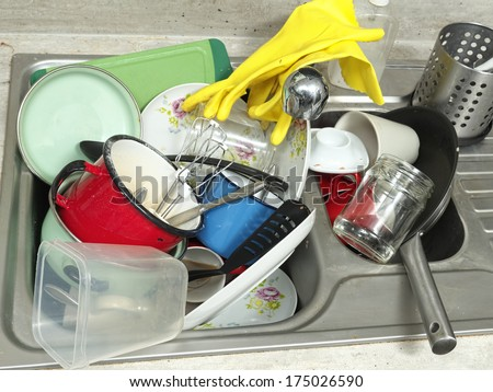 Kitchen sink full of dirty kitchenware - stock photo