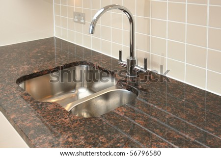 Kitchen sink with granite work surface. - stock photo