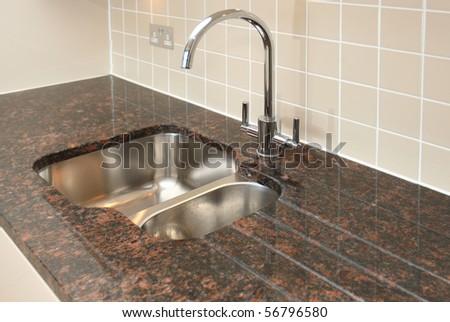 Kitchen sink with granite work surface. - stock photo