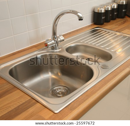 Kitchen sink with mixer tap - stock photo