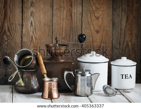 Kitchen still life.  Vintage coffee grinder, coffee pot and tea pot on a wooden wall background