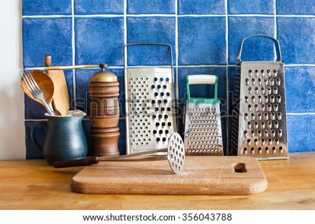 Kitchen still life. Vintage utensils. kitchenware graters, ceramic jug, wooden spoons. cutting board. Blue tiles wall. wooden table background - stock photo