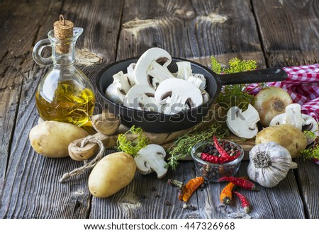 Kitchen still-life with mushrooms in a black cast iron skillet, new potatoes, garden herbs, onions and garlic on a wooden background. The concept of a healthy home food