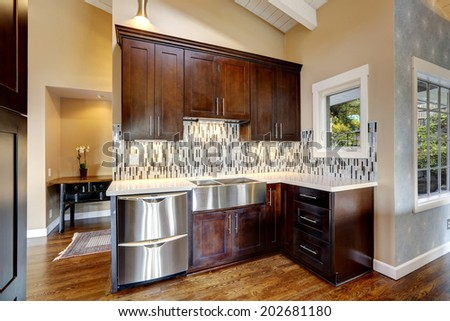 Kitchen storage combination in dark brown color with steel stainless appliances - stock photo