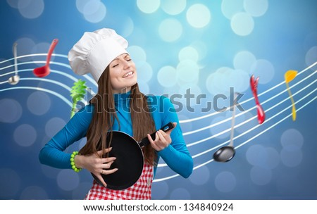 Kitchen symphony concept. Pretty young woman in chef's hat and apron playing pan like guitar with notes-ladles on background