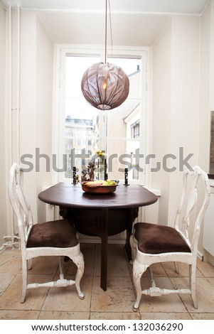 kitchen table by the window and two antique chairs - stock photo