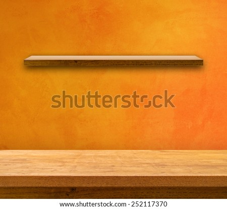 Kitchen table on orange painted wall with shelf - stock photo