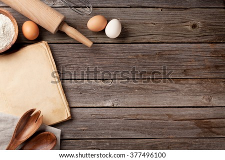 Kitchen table with blank vintage recipe cooking book, utensils and ingredients. Top view with copy space - stock photo