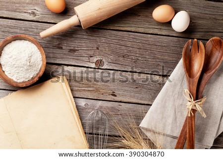 Kitchen table with cookbook, utensils and ingredients. Top view with copy space - stock photo