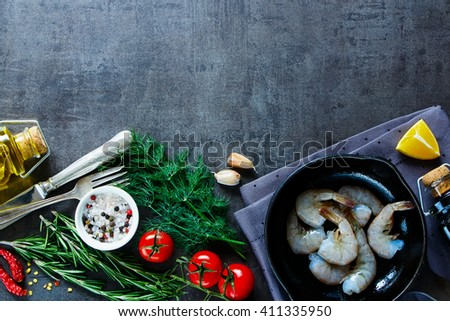 Kitchen table with raw ingredients for preparing fresh seafood (shrimp, tomatoes, fresh herbs and spices) on dark vintage background, top view, space for text. - stock photo
