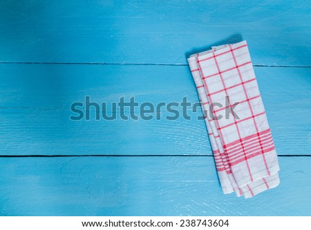 Kitchen towel red on blue wooden background. - stock photo