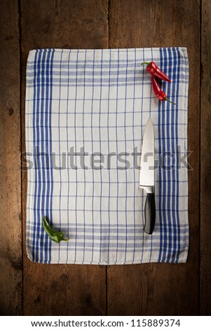 Kitchen towel with red and green chilies with a knife. - stock photo