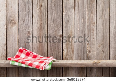 Kitchen towels on shelf against rustic wooden wall. View with copy space - stock photo